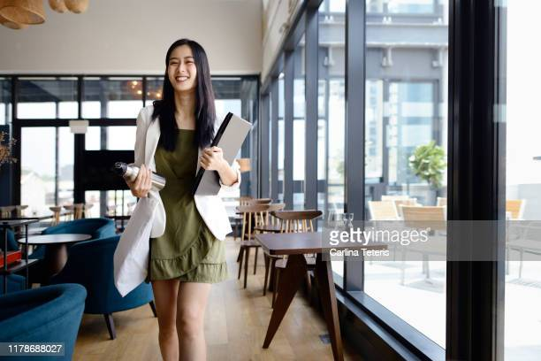 Business woman walking into work with computer and water bottle