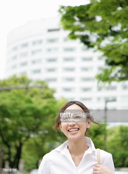 Business woman walking on road, smiling
