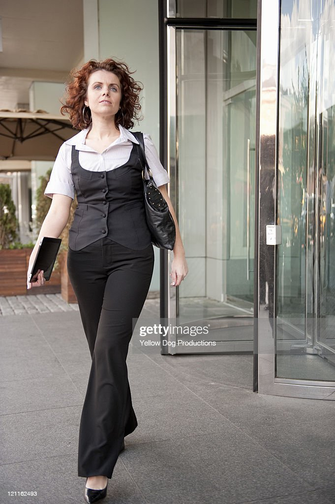 Business woman walking out of office building : Stock Photo
