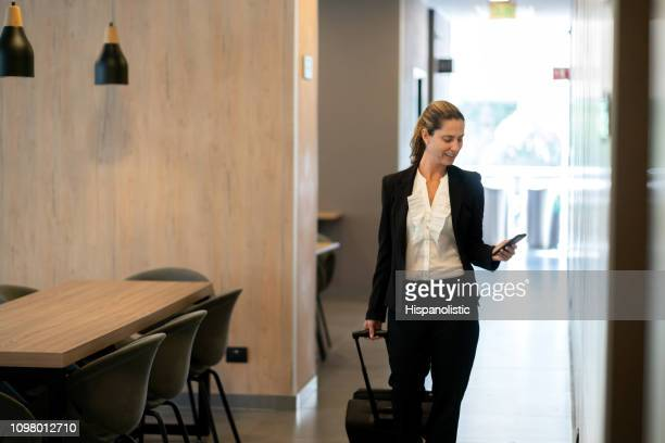 business woman walking through hotel corridor pulling her suitcase while chatting on smartphone smiling - hispanolistic stock photos and pictures
