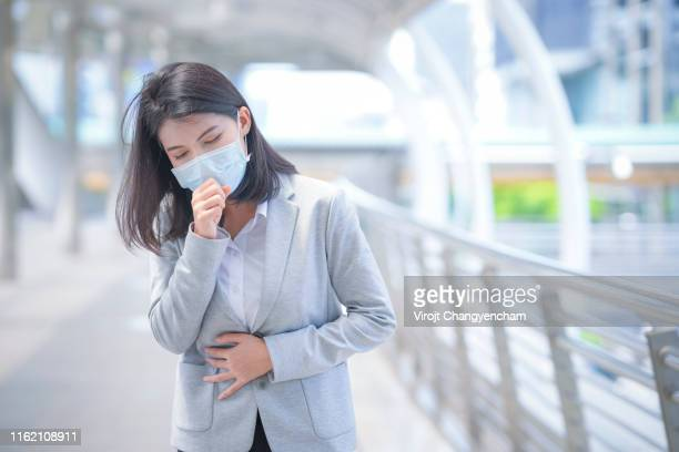 business woman wear face mask and coughing while standing in the town - virus bildbanksfoton och bilder