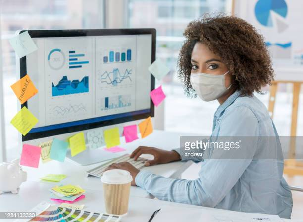 business woman wearing a facemask while working at the office - biosecurity stock pictures, royalty-free photos & images
