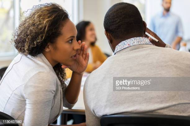 business woman whispers in colleague's ear - whispering stock pictures, royalty-free photos & images
