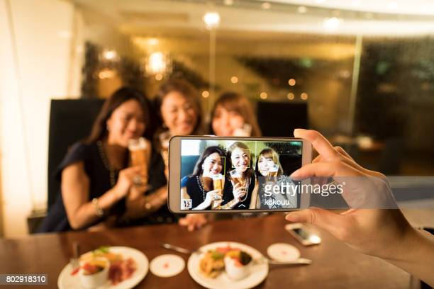 a business woman who takes pictures with a smartphone. - girls night stock photos and pictures