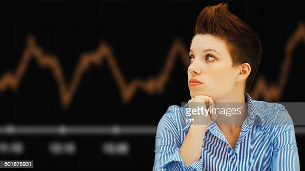 Business woman with a punk hairstyle in front of a stock exchange board