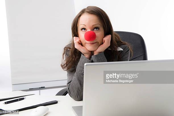 business woman with a red clown nose - sad clown stock photos and pictures