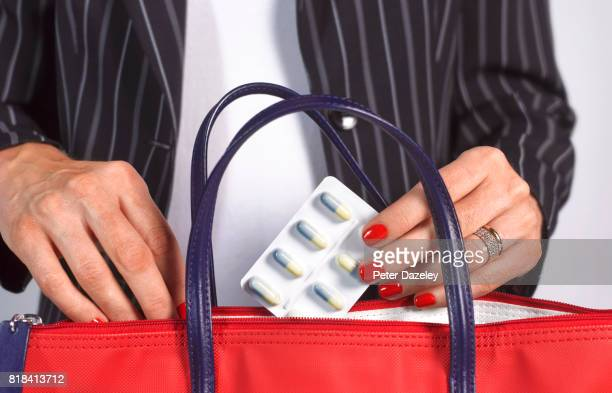 business woman with anti-depressants in her handbag - clutch bag stock pictures, royalty-free photos & images