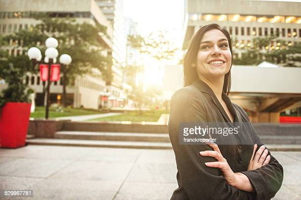 business woman with arm crossed looking away at sunset
