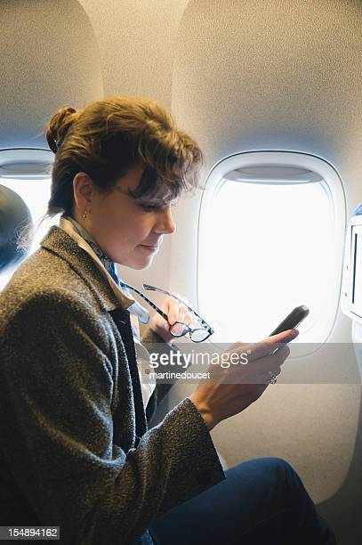 "business woman with cell phone in plane. - ""martine doucet"" or martinedoucet stock pictures, royalty-free photos & images"