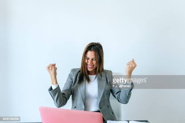 business woman with expression of triumph in the office - éxito fotografías e imágenes de stock