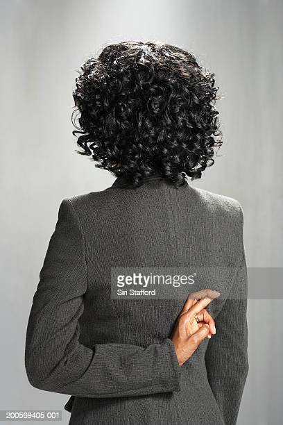 business woman with fingers crossed behind back - falsenews stock pictures, royalty-free photos & images