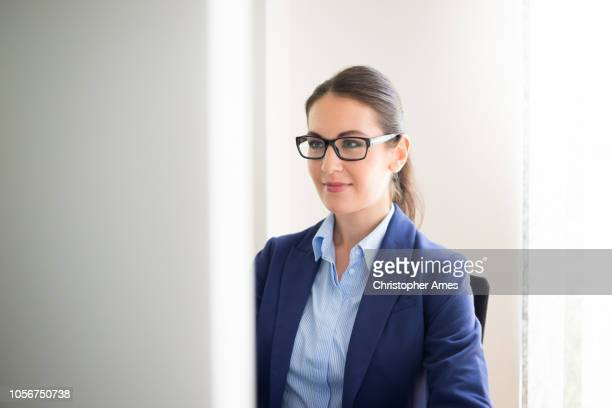 business woman with glasses using computer - blue suit stock pictures, royalty-free photos & images