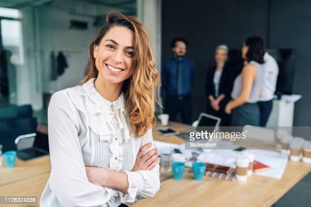 zakenvrouw met zijn ploeg achter - goed gekleed stockfoto's en -beelden
