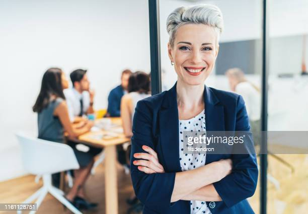 business woman with his team behind - short hair stock pictures, royalty-free photos & images