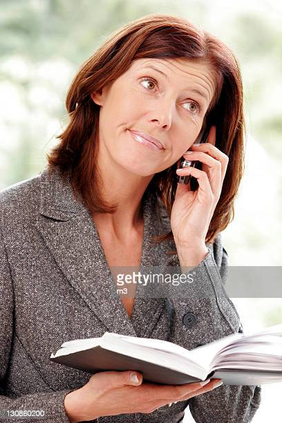 Business woman with mobile phone, under stress, with an appointement calendar