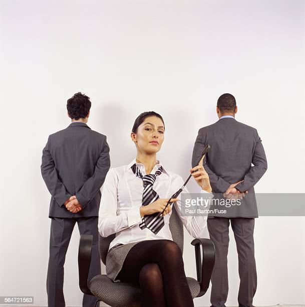 business woman with whip sitting in front of two men - women whipping men stock photos and pictures