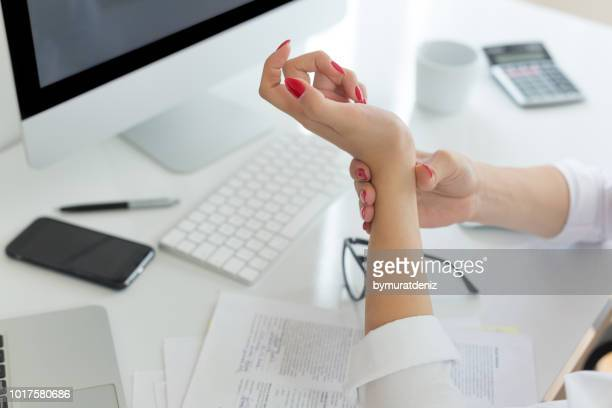 business woman with wrist pain - pain foto e immagini stock