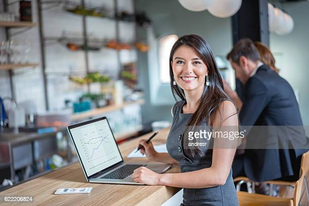 business woman working at a cafe - gerente - fotografias e filmes do acervo