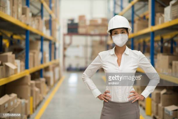 business woman working at a distribution warehouse wearing a facemask to avoid covid-19 - prevention stock pictures, royalty-free photos & images