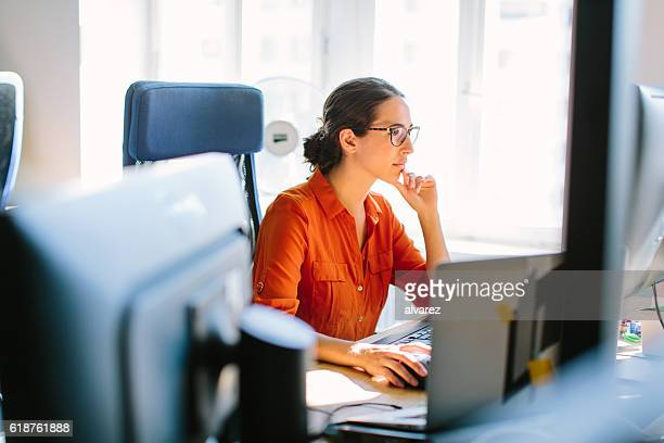 business woman working at her desk - desktop pc stockfoto's en -beelden