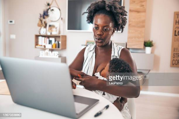 business woman working at home and taking care of her two daughters - breastfeeding stock pictures, royalty-free photos & images