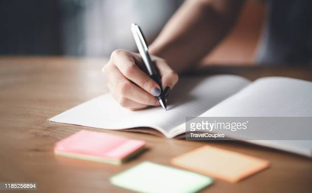 business woman working at office with documents on his desk, business woman holding pens and papers making notes in documents on the table, hands of financial manager taking notes - bericht stockfoto's en -beelden