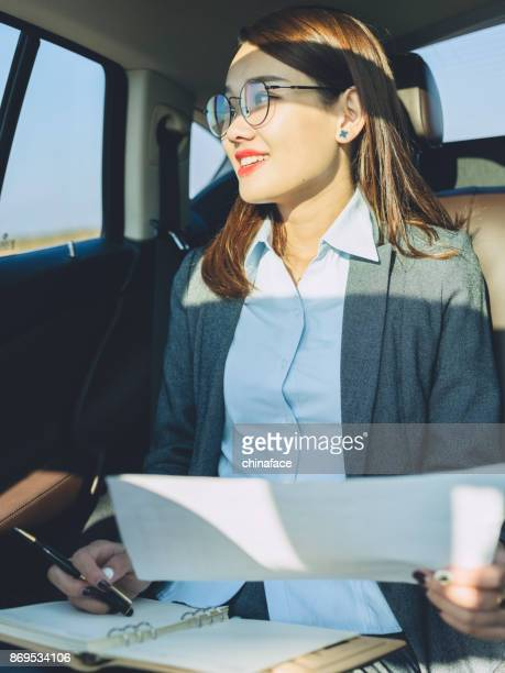business woman working in car with paperwork
