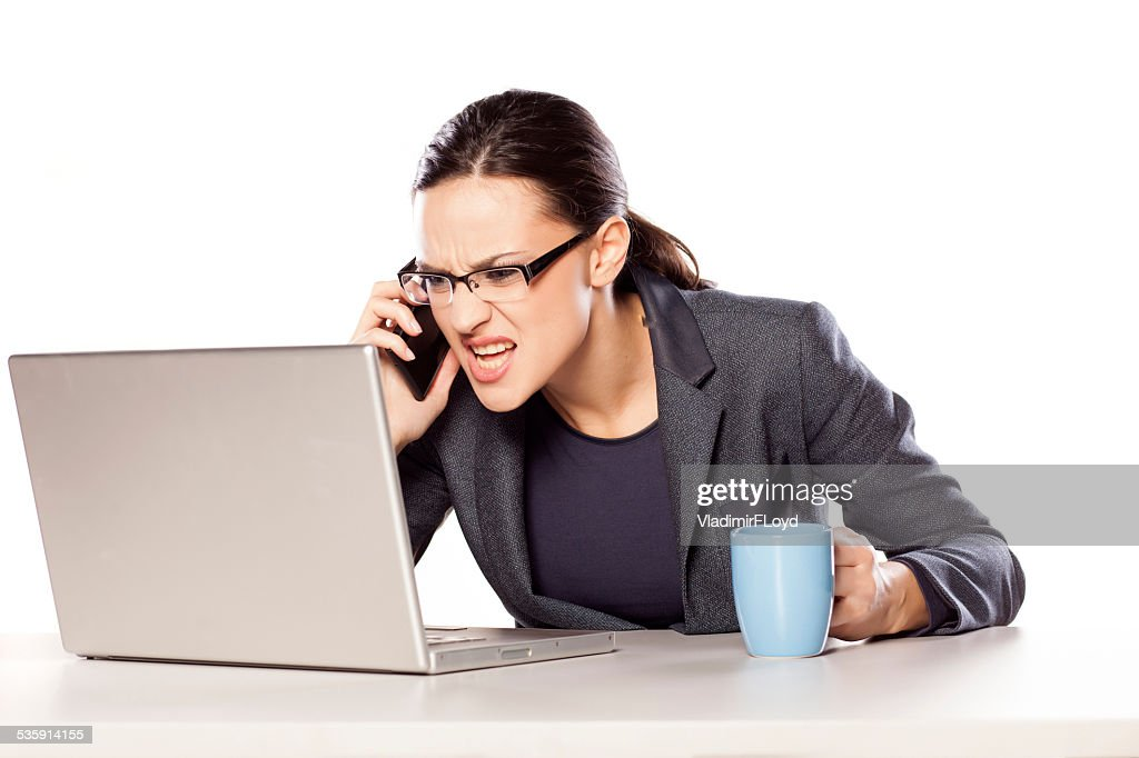 Business woman working on laptop and arguing on the phone : Stock Photo