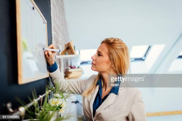 Zakenvrouw schrijven op het whiteboard in haar kantoor
