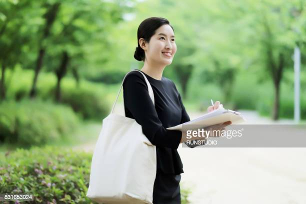 business woman writing something on clipboard in the park