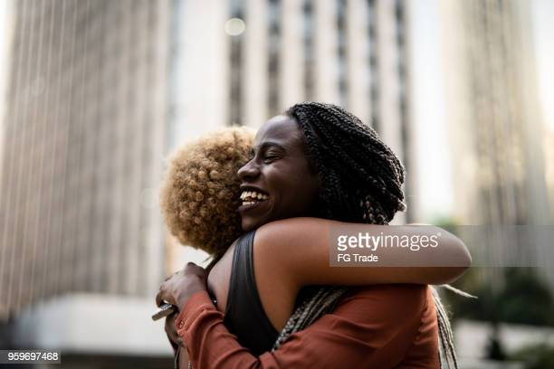 mulher de negócios/estudantes abraçando - abraçar - fotografias e filmes do acervo