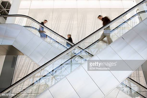 Business women and man on escalator