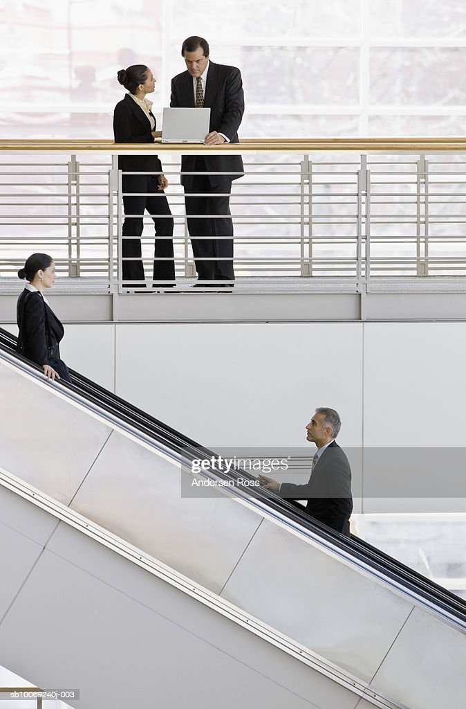 Business women and man working on laptop, man and woman on escalator in foreground : Stockfoto