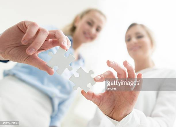 Business women assembling pieces of a puzzle