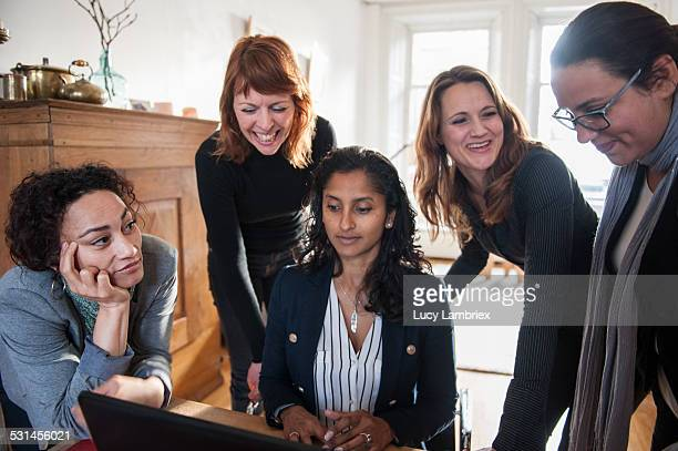 Business women at meeting, gathered around laptop