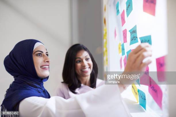 business women brainstorming with sticky notes - islam stock pictures, royalty-free photos & images