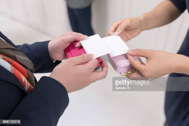 business women exchanging business cards - business cards stock photos and pictures