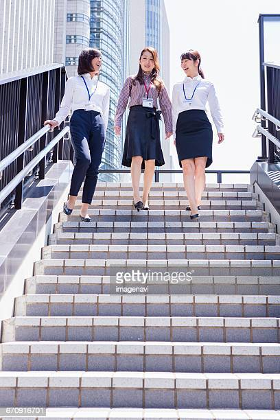 business women going down the stairs at downtown area - down blouse stockfoto's en -beelden