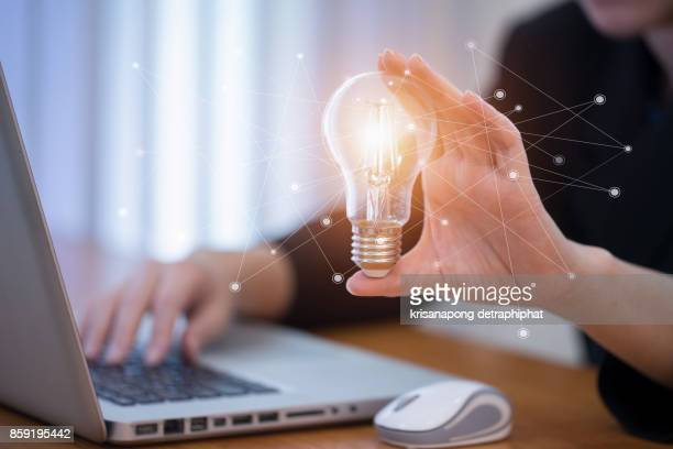 Business women holding light bulbs, ideas of new ideas with innovative technology and creativity.