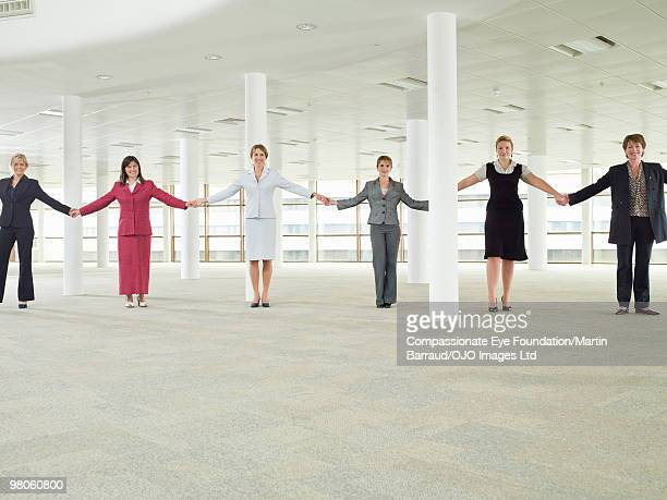 business women in a line holding hands