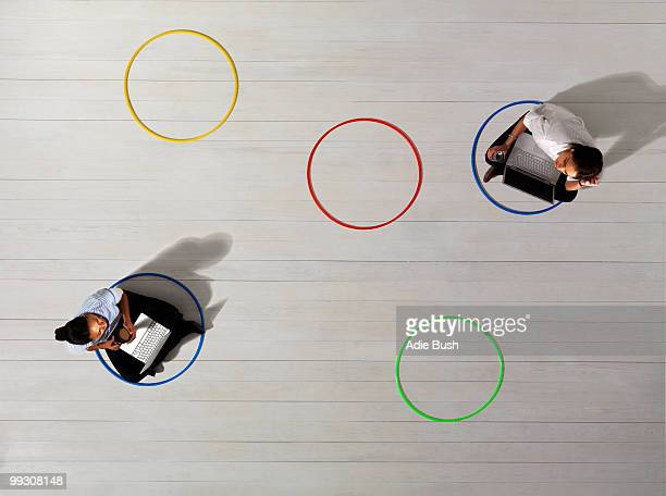 business women in circles with laptops - social distancing stock-fotos und bilder