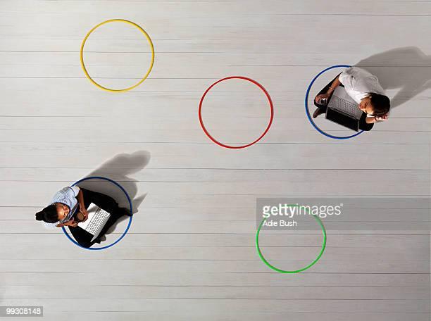 business women in circles with laptops - abstand halten stock-fotos und bilder