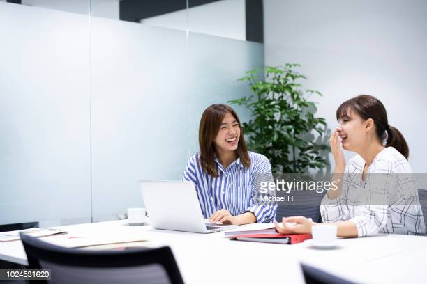 business women looking at computer in office - two people ストックフォトと画像