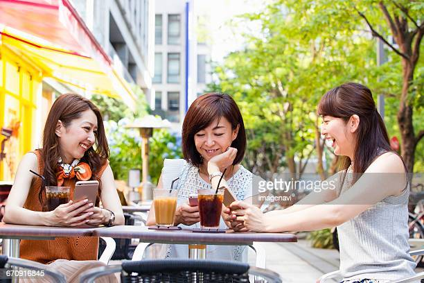 Business women operating their smart phone at an outdoor cafe