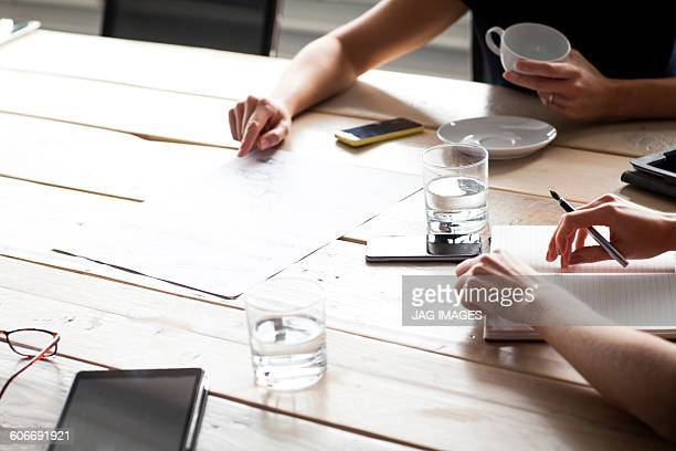 business women pointing at paperwork designs