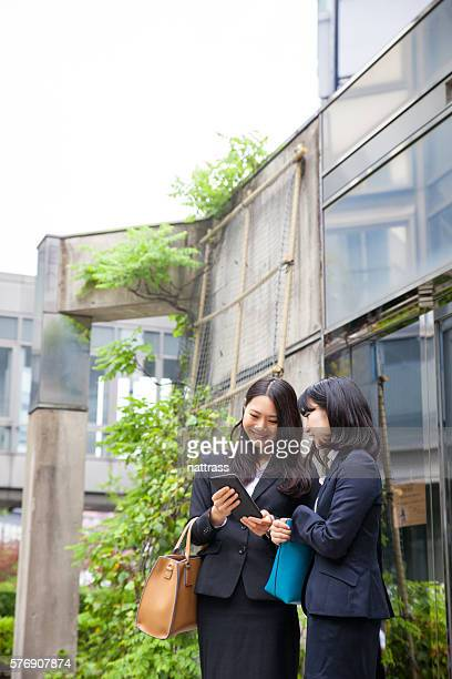 Business women showing her colleague work on her tablet