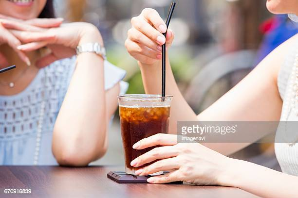 Business women sitting at an outdoor cafe and iced coffee