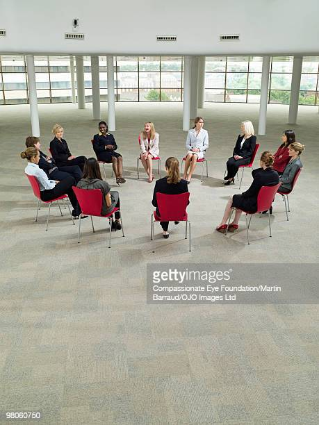 business women sitting in a circle talking