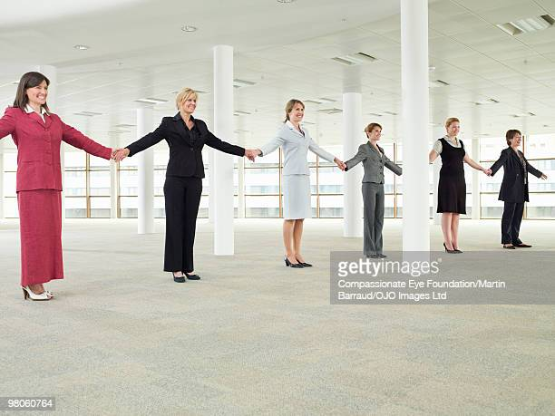 business women standing in a line holding hands