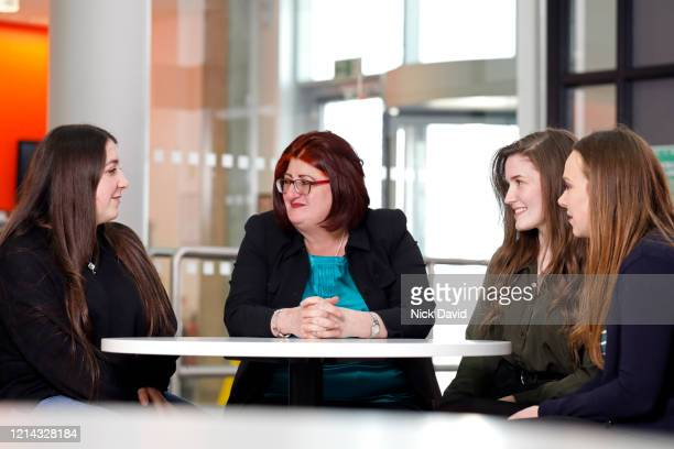a business women talking to young female college students in a bright modern university. - femalefocuscollection stock pictures, royalty-free photos & images